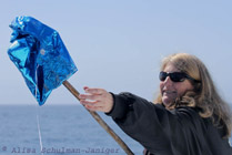 Nancy Black collecting a mylar balloon from the ocean